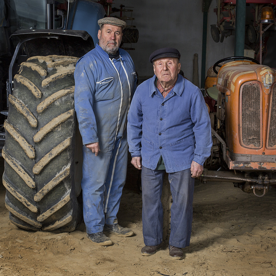 Full-length portrait of a father and his son on the farm in front of their tractors. Portrait de plein pied d'un père et son fils à la ferme devant leurs tracteurs.