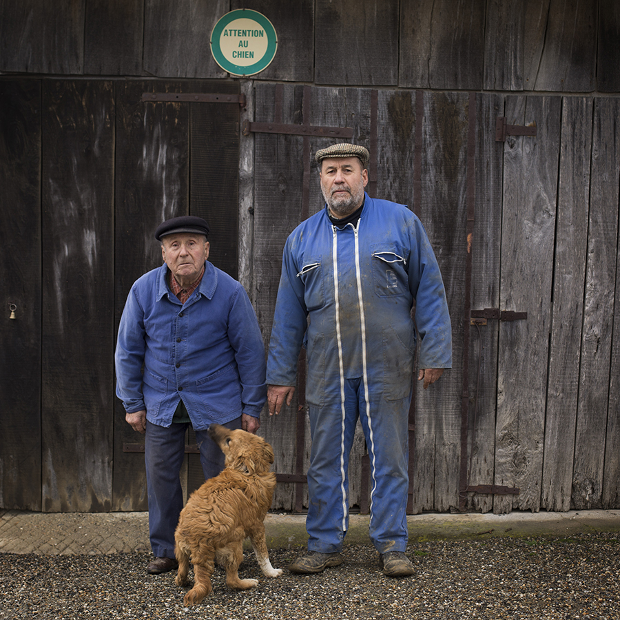 Full-length portrait of a father and his son at the farm. Portrait de plein pied d'un père et son fils à la ferme.