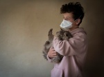 Portrait of a teenage boy with a mask and his cat during lockdown. Portrait d un adolescent avec un masque et son chat pendant le confinement.