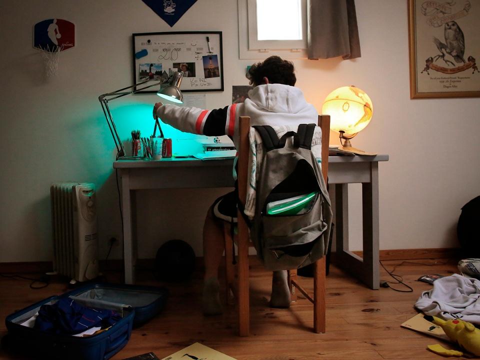 Portrait of a teenage boy behind his desk doing his school homework. Portrait d un adolescent derriere son bureau qui fait ses devoirs d ecole