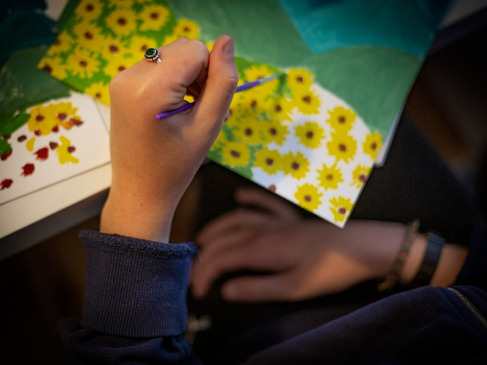 A girl paints a landscape with flowers. Une fille peint un paysage avec des fleurs.