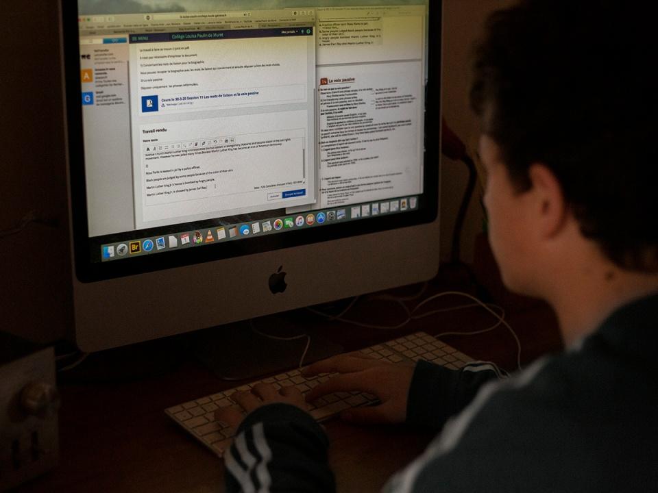 Portrait of a teenage boy in front of a computer screen doing his school homework. Portrait d un adolescent devant un ecran d ordinateur qui fait ses devoirs d ecole