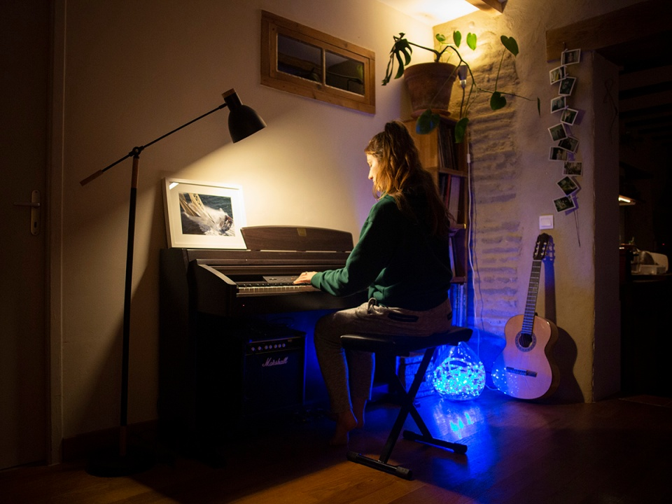 A girl plays the piano in the evening in a house. Une fille joue du piano le soir dans une maison.